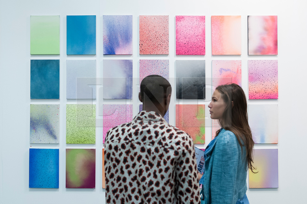 """© Licensed to London News Pictures. 19/05/2016. London, UK. A couple view Zane Lewis's """"Lacquer on Canvas"""".  Art16 opens at Olympia, in west London.  Now in its fourth edition, the fair brings together over 100 galleries from more than 30 countries showcasing a diverse cross-section of work by contemporary artists from around the world for buyers and art enthusiasts to visit. Photo credit : Stephen Chung/LNP"""