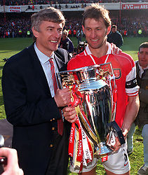 Jubiliant Arsenal manager Arsene Wenger (left) and captain Tony Adams hold the FA Carling Premiership League trophy which was presented to them following their 4-0 victory over Everton.