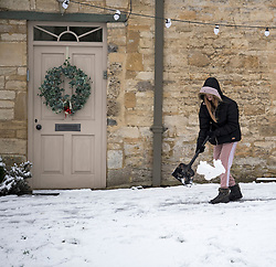 © Licensed to London News Pictures. 28/12/2020. Burford, UK. A woman clears snow from the pavement in front of a residential property in the village of Burford in Oxfordshire, south England as the UK experiences freezing temperatures over night. Photo credit: Ben Cawthra/LNP