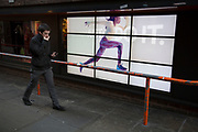 "Nike advertising runner runs along a barrier near unsuspecting people. The video advert with the slogan 'Just Do It"" with a woman running across the screen makes for an optical illusion of sorts and a strange urban scene. London, UK."