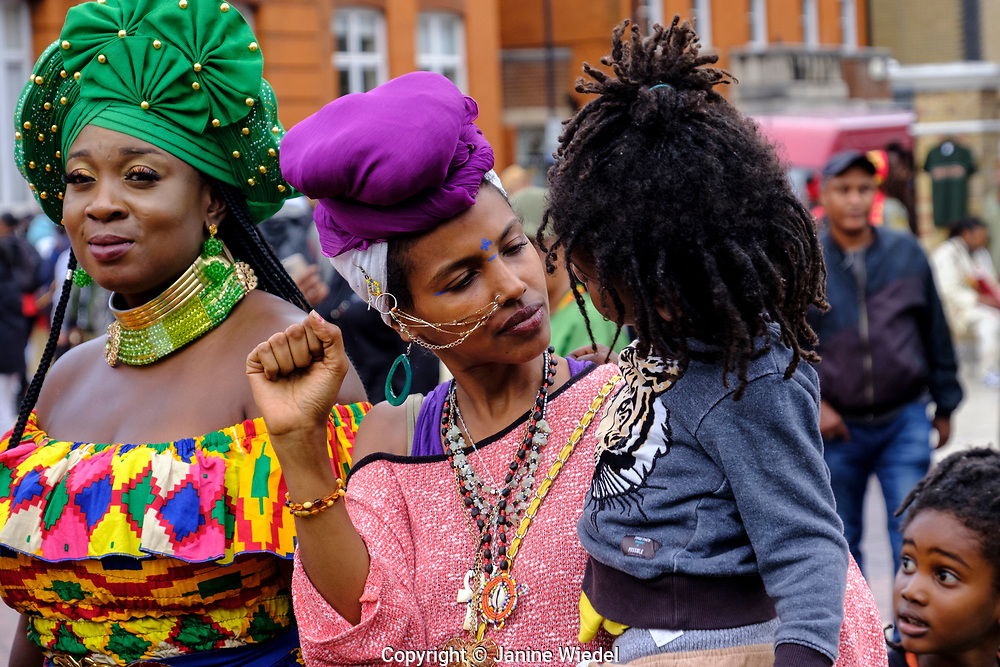 Marvina Newton (left) and Rasta woman with 2 children at at annual Reparation Rebellion event on Afrikan Emancipation Day in Windrush Square Brixton 2021.