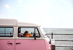 Back View of Young Man Looking at Ocean from Camper Van Window
