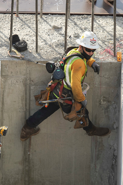 Austin, TX USA July 14, 2020: Construction worker Emmanuel Quevedo prepares an elevator shaft for additional bracing during an eight-hour shift in the 105-degree Texas heat.  Crews are on the second story of a planned 53-story building as they take precautions against the coronavirus pandemic.