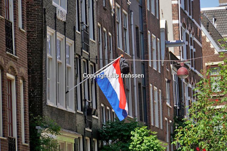 Nederland, Amsterdam, 7-5-2020 Nederlandse vlag met schooltas aan de stok is uitgehangen om te vieren dat het eindexamen is gehaald.  Door de coronacrisis worden de eindexamens anders gehouden als normaal en is er geen centraal schriftelijk examen . Bij veel geslaagden gaat traditioneel de vlag uit, met de boekentas aan het einde van de stok. Foto: Flip Franssen