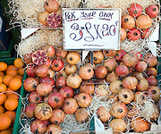 Pomegranates for sale on market stall three for one pound twenty pence
