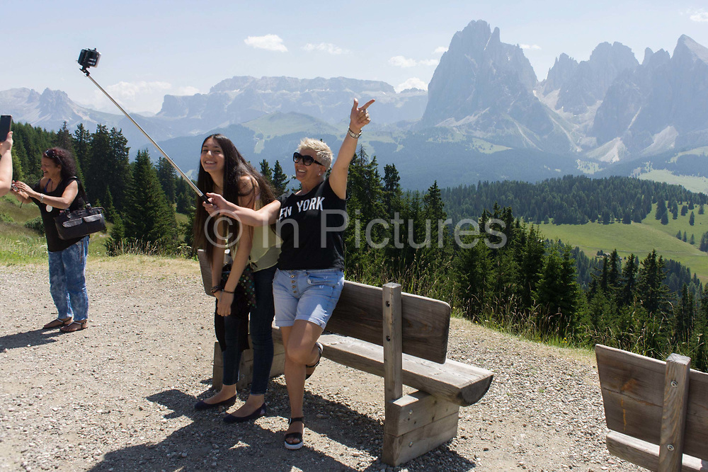 Visitors look out over the Alpe di Siusi (German: Seiser Alm) at the top of the cable car station at Piz Sorega, above the South Tyrolean town of Ortisei-Sankt Ulrich in the Dolomites, Italy. Standing at the highest point of the vast grassland meadow, they take photos and admire the panoramic scenery. The Alpe di Siusi is the biggest high-alpine pasture in Europe with a surface of 57 km² and its altitude range from 1680 to 2350 m above sea level. This high-alpine pasture is located in the heart of the Dolomites surrounded by the Sasso Lungo Mountain Group, the Sciliar Nature Park, and the Catinaccio Mountain Group, the Northern Alps and the Sciliar Mountain Massif with Santner Peak.