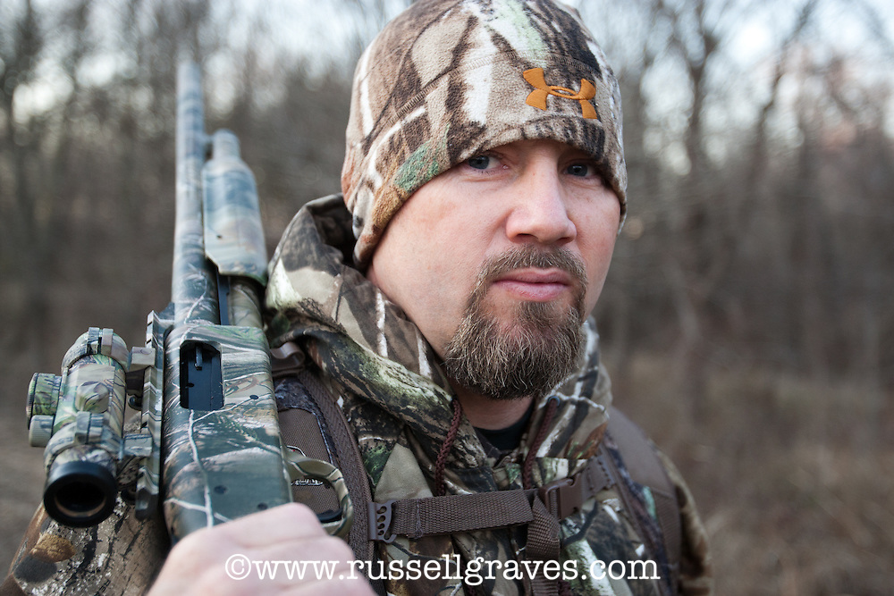 PORTRAIT OF A SHOTGUN HUNTER WEARING REALTREE AP CAMOUFLAGE AND HOLDING A MOSSBERG SHOTGUN WITH A HOLOGRAPHIC SCOPE