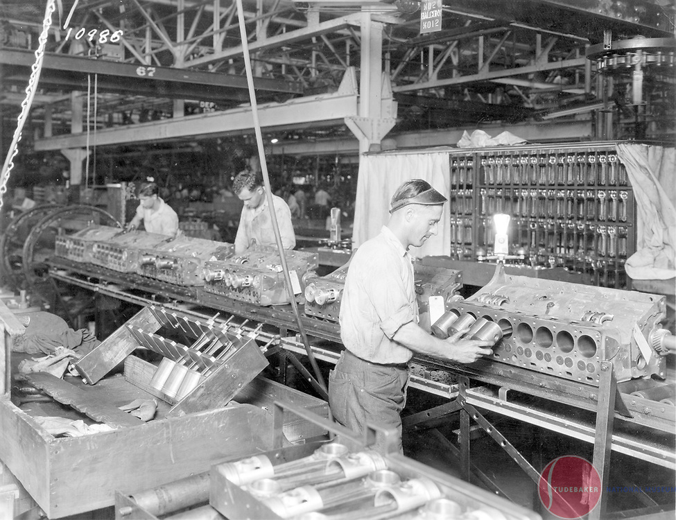 Studebaker engine assembly, 1930.  Studebaker workers assemble the Commander/Dictator inline eight cylinder engine.