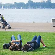 Nederland Rotterdam 27 september 2009 20090927.                                                                                    .Promenade Kralingse Plas, 2 meiden liggen te niksen op een grasveld en genieten van zomerweer.  People  enjoying sunny weather in parc..Foto: David Rozing