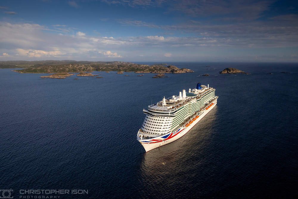 """Immediate release: Monday August 9, 2021 - Editorial free to use image<br /> <br /> 'A new era in travel' as P&O Cruises Iona makes maiden voyage to namesake island<br /> <br /> Britain's largest and most environmentally-friendly cruise ship, P&O Cruises Iona, has embarked on its maiden voyage visiting its Scottish namesake island with a fireworks display tonight as the highlight of celebrations.<br /> <br /> P&O Cruises President Paul Ludlow said: <br /> <br /> """"Iona's maiden voyage is the start of a new era in travel as Britain's most environmentally-friendly cruise ship, the first in the country powered by liquefied natural gas, sets sail.<br /> <br /> """"For this special maiden voyage we wanted to bring guests to the island of Iona which has influenced many aspects of the ship – the sense of space in the SkyDome through to our gin still named """"Columba"""", the heather in our Marabelle gin distilled on board, and, of course, its name.""""<br /> <br /> Iona's first-ever cruise is currently sailing around the UK coast for seven nights, having departed the home port of Southampton on August 7, 2021.<br /> <br /> The ship is at anchor adjacent to the island of Iona ahead of commencing scenic cruising around the Isle of Colonsay, Lochbuie, Duart Castle, Tobermory, Bac Mòr, Fingal's Cave, Sound of Jura, Claggain Bay, Mull of Kintyre and Sanda Island.<br /> <br /> Iona features the first gin still on a cruise ship, created in association with Salcombe Gin, distilling tailor made spirit on board. The gin's maiden production will take place in Iona's custom-made still and will be distilled, bottled and labelled on board.<br /> <br /> Gary Barlow is music director of Iona's 710 Club. This atmospheric late-night music venue will offer an opportunity for up-and-coming musicians to get their break.<br /> <br /> Spectacular aerial shows have also been especially devised for Iona, the brainchild of Canadian entertainment company Creativiva. The ship's stunning design, featuring a two-d"""