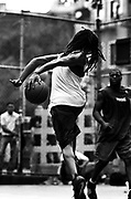 June 10th 2003. New York, New York. United States..Located in the heart of Greenwich Village, the West 4th Street basketball Court, known as ?The Cage?, offers no seating but attracts the best players and a lot of spectators as soon as spring is around the corner..Half the size of a regular basketball court, it creates a fast, high level of play. The more people watch, the more intense the games get. « The Cage » is a free show. Amazing actions, insults and fights sometimes, create tensions among and inside the teams. The strongest impose their rules. Charisma is present..?The Cage? is a microcosm. It?s a meeting point for the African American street culture of New York. Often originally from Jamaica or other islands of the Caribbean, they hang out, talk, joke, laugh, comment the game, smoke? Whether they play or not, they?re here, inside ?The Cage?. Everybody knows everybody, they all greet each other, they shake hands and hug: ?Yo, whasup man??.