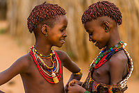 Two young Hamer tribe girls express their friendship, Omo Valley, Ethiopia.