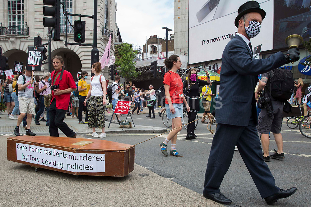A man dressed as an undertaker pulls a coffin representing care home residents who have died during the Covid-19 pandemic on the United Against The Tories national demonstration organised by the Peoples Assembly Against Austerity in protest against the policies of Prime Minister Boris Johnsons Conservative government on 26th June 2021 in London, United Kingdom. The demonstration contained blocs from organisations and groups including Palestine Solidarity Campaign, Stand Up To Racism, Stop The War Coalition, Extinction Rebellion, Kill The Bill and Black Lives Matter as well as from trade unions Unite and the CWU.