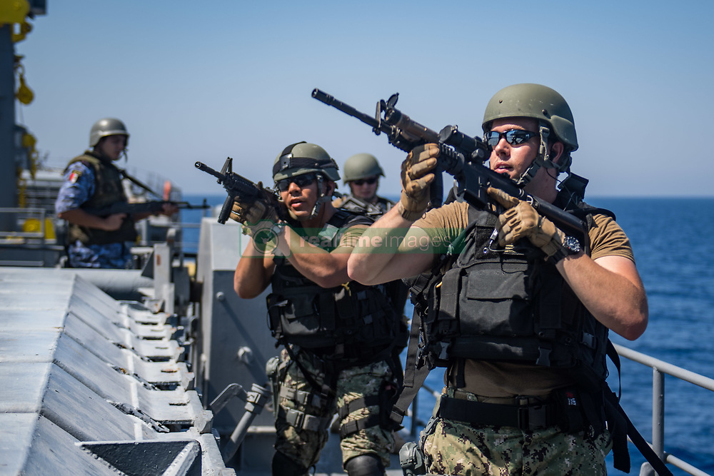 RED SEA (July 31, 2018) U.S. Navy Lt. j.g. Sean Hudgins, right, and Gunner's Mate Stephen Barahona, members of a visit, board, search and seizure (VBSS) team assigned to the guided-missile destroyer USS Jason Dunham (DDG 109), tactically move aboard an Egyptian Naval Force (ENF) supply ship with an ENF VBSS team during an integrated-team VBSS evolution as part of exercise Eagle Salute 18. Eagle Salute 18 is a surface exercise with the ENF conducted to enhance interoperability and war-fighting readiness, fortify military-to-military relationships and advance operational capabilities of all participating units. Jason Dunham is deployed to the U.S. 5th Fleet area of operations in support of naval operations to ensure maritime stability and security in the Central region, connecting the Mediterranean and the Pacific through the western Indian Ocean and three strategic choke points. (U.S. Navy photo by Mass Communication Specialist 3rd Class Jonathan Clay/Released)180731-N-UX013-1185