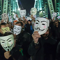 Participants march through Liberty Bridge during a local event of the million masked march movement in central Budapest, Hungary on November 05, 2014. ATTILA VOLGYI