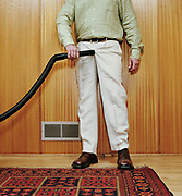 Man holding vacuum hose to pants crotch, low section