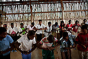 """Children from Mulungo rural primary school, practice a dance singing a song that says """"Beware, AIDS can kill"""" before a presentation to other schoolmates, during an HIV prevention campaign organized by CARE,  part of a national education program. Mulungo, west of Vilanculos, Mozambique, Aug. 2009.  Knowledge about HIV and HIV prevention greatly improved in the last years among youth, however, knowledge about means of transmission is still low."""