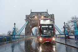 © Licensed to London News Pictures. 10/12/2017. London, UK. A bus crosses Tower Bridge during heavy snow fall. Heavy snow has fallen across the UK this morning. Photo credit: Vickie Flores/LNP