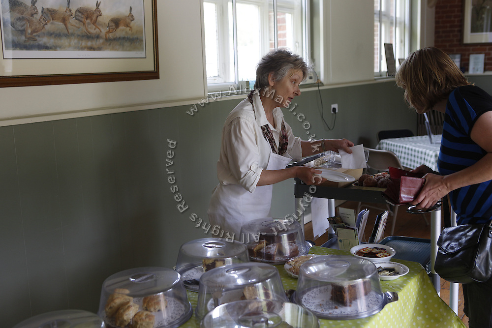 A tourist is purchasing a cup of tea in Thixendale, Yorkshire, England, United Kingdom.