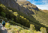 Hiker and waterfall, Routeburn Track, South Island, New Zealand