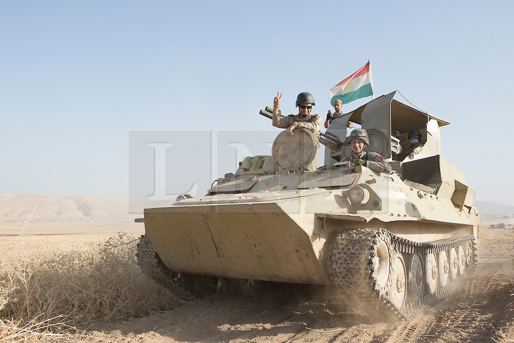 20/10/2016. Bashiqa, Iraq. The commander of a Kurdish armoured personnel carrier flashes a V for victory sign as peshmerga fighters launch an offensive to retake the Bashiqa area from Islamic State militants today (20/10/2016).<br /> <br /> Launched in the early hours of today with support from coalition special forces and air strikes, the attack is part of the larger operation to retake Mosul from the Islamic State, and involves both the Kurds and the Iraqi Army. The city of Bashiqa, around 9 miles north of Mosul, is one of several gateway areas that must be taken before any attempted offensive on Mosul itself.<br /> <br /> Despite the peshmerga suffering several casualties after militants fought back using mortars, heavy machine guns and snipers, the Kurdish forces were quickly taking ground with Haider al-Abadi, the Iraqi prime minister, stating that the operation to retake Mosul was progressing faster than expected. Photo credit: Matt Cetti-Roberts/LNP