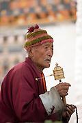 Buddhist spinning a hand held prayer wheel, Bhutan