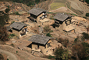 Traditional three-story houses built of rammed earth in the hillside village of Shingkhey, Bhutan. Nalim and Namgay's house is center, top. Their neighbor (to the right) is building a new house for his family directly in front of the old one. Carpenters from another village build the wooden structures such as doorways, rafters, windows, and lintels. From coverage of revisit to Material World Project family in Bhutan, 2001.