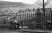 Two local children squeeze through railings of the  unkempt cemetery attached to the Blaenau Baptist Church in the south Wales town of Abertillery (Welsh: Abertyleri). The kids have walked their dog through this field filled with old headstones and graves, playing safely in the open-air of this Welsh community. Rows of terraced Victorian homes line the distant end of this ground and then clinging to far hill side and beyond. Its population rose steeply during the period of (now defunct) mining development in South Wales, being 10,846 in 1891 and 21,945 ten years later. Lying in the mountainous mining district of the former counties of Monmouthshire and Glamorganshire, in the valley of the Ebbw Fach. In 2003, Abertillery was found to have the cheapest house prices in the United Kingdom, according to a survey by the Halifax Building Society.
