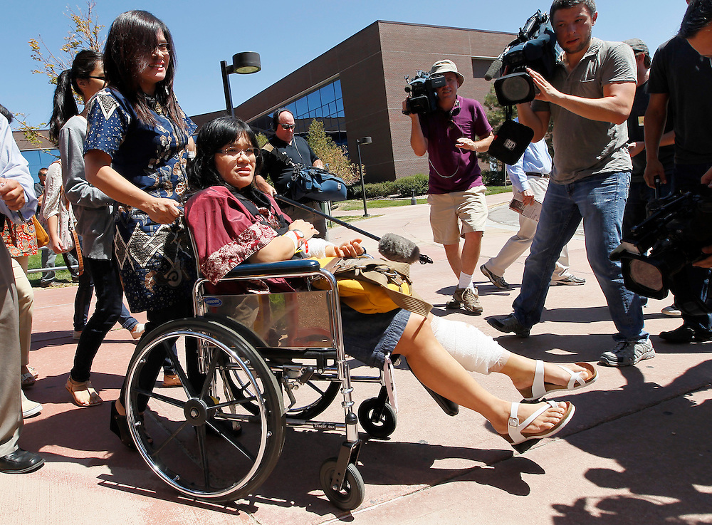 Rita Paulina, shot twice in the arm and once in the leg leaves the second court appearance of James Holmes, the accused shooter in the July 20, 2012 theater shootings in Centennial, Colorado July 30, 2012. Holmes was formally charged on Monday with 24 counts of first-degree murder and 116 counts of attempted murder.  REUTERS/Rick Wilking (UNITED STATES)