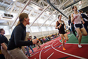 Grinnell Assistant Coach Jen Jacobsen, left, yells split times to Ben Tyler '14 during the Distance Medley Relay on Friday of the Midwest Conference Championships.