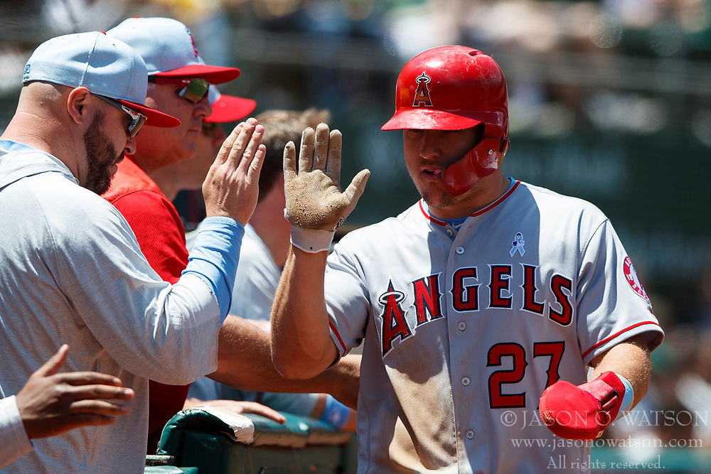 OAKLAND, CA - JUNE 17: Mike Trout #27 of the Los Angeles Angels of Anaheim is congratulated by teammates after scoring a run against the Oakland Athletics during the third inning at the Oakland Coliseum on June 17, 2018 in Oakland, California. The Oakland Athletics defeated the Los Angeles Angels of Anaheim 6-5 in 11 innings. (Photo by Jason O. Watson/Getty Images) *** Local Caption *** Mike Trout