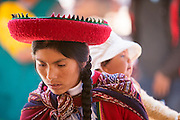 Quechua woman in traditional dress carrying child, Chinchero Town Sunday Market, Cusco region, Peru, South America