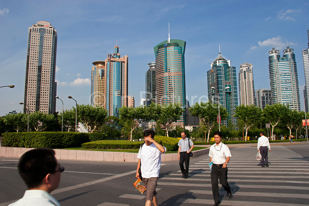 Businessmen cross the street walking towards Pudongs main financial district Lu Jia Zui, Pudong in Shanghai, China. This centre for Shanghai, and even Chinas finances has developed from nothing since the mid to late 1990s. Now it is a place to see businessmen in crisp white shirts and suits, carrying brief cases.