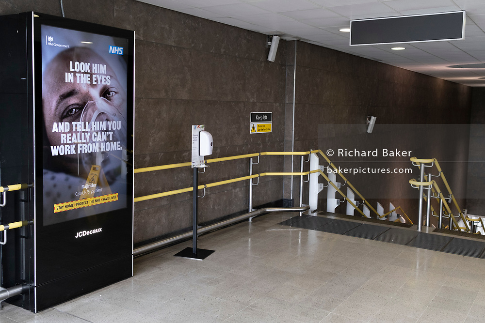 A government NHS (National Heath Service) ad displaying the face of a Covid patient, is at the top of steps at a deserted Blackfriars rail station during the third lockdown of the Coronavirus pandemic, in the 'City of London', the capital's financial district, aka The Square Mile, on 2nd February 2021, in London, England.