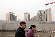 A couple walks past a construction site for new apartment buildings in Shanghai, China on 19 January, 2009.  Real estate prices in China have risen rapidly in recent years despite government's repeated promise of action to cool the property sector.
