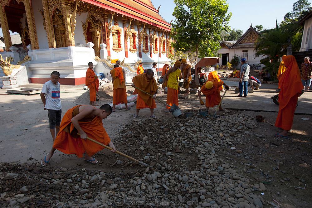 Monks and novices working rebuilding their temple compound in Luang Prabang, Laos.