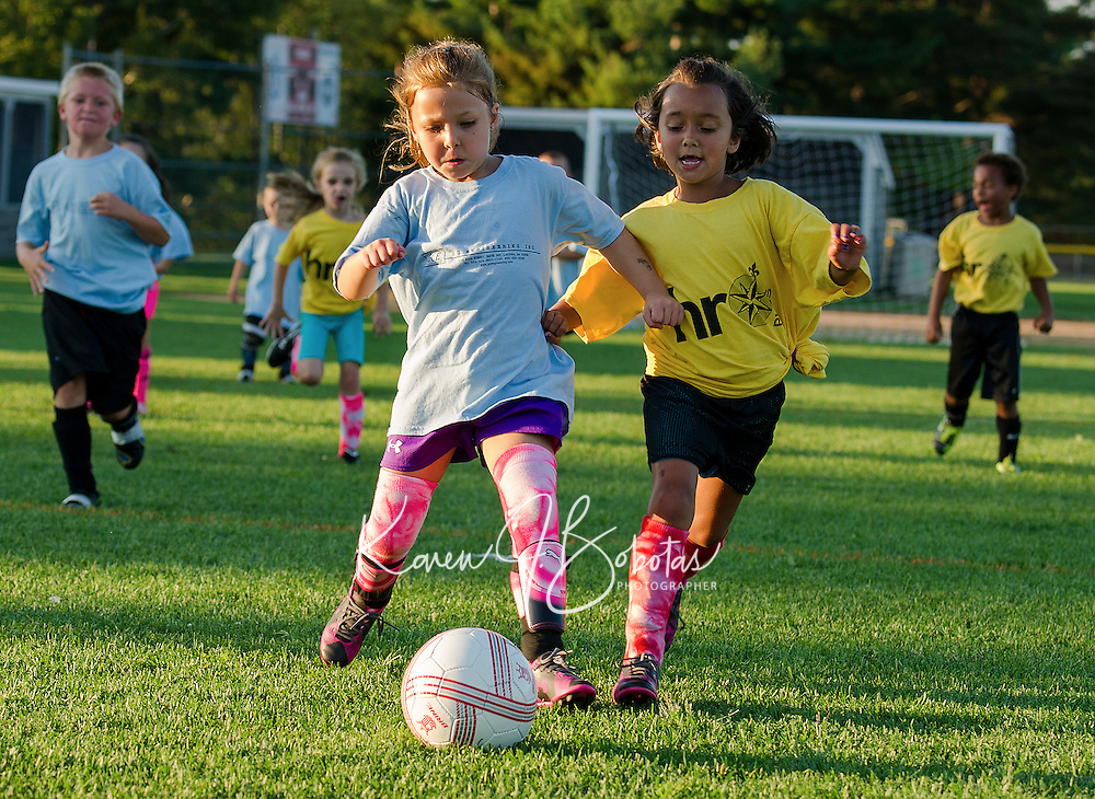 Kailey Knott of GC Engineering and Sophia Dewhirst of HRO Plus go after the ball in the Laconia Youth Soccer U8 division at Opechee Park on Wednesday evening.  (Karen Bobotas/for the Laconia Daily Sun)