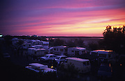 Sunset and night skies. Caravan sites camping for gens de voyages, Roma,  Gitan and maounche at Saintes Maries de la Mer for the Gypsy festival<br /><br />Europe, France, Camargue, Saintes Maries de la Mer. The seaside town in the Camargue hosts a Gypsy festival once a year during May, where its landscape undergoes great changes. Otherwise it is a land bordered by sea, lakes and ponds, populated by flamengos, bulls and horses.