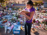 "15 JANUARY 2010 - TUCSON, AZ:    ALYSIA SIMMONS writes a note for Congresswoman Gabrielle Giffords at a memorial in front of the Congresswoman's office in Tucson, AZ, Saturday, January 15. Six people were killed and 14 injured in the shooting spree at a ""Congress on Your Corner"" event hosted by Arizona Congresswoman Gabrielle Giffords at a Safeway grocery store in north Tucson on January 8. Congresswoman Giffords, the intended target of the attack, was shot in the head and seriously injured in the attack but is recovering. Doctors announced that they removed her breathing tube Saturday, one week after the attack. The alleged gunman, Jared Lee Loughner, was wrestled to the ground by bystanders when he stopped shooting to reload the Glock 19 semi-automatic pistol. Loughner is currently in federal custody at a medium security prison near Phoenix.    PHOTO BY JACK KURTZ"