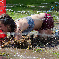 Competitor crawls through muddy water under barbed wire during the Brutal Run extreme obstacle course race in Budapest, Hungary on August 30, 2014. ATTILA VOLGYI