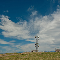 Cirrus & lenticular clouds soar over telephone microwave towers near Livingston, Montana. The Crazy Mountains rise behind.