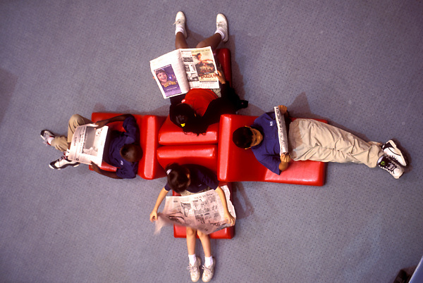 Stock photo of children sitting and reading in library chairs