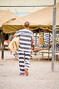 """17 JULY 2006 - PHOENIX, AZ: An inmate carries his bedding across the yard before the National Anthem was played in """"Tent City"""" in the Maricopa County Jail in Phoenix, AZ. There are about 650 inmates living in the tents. Maricopa County Sheriff Joe Arpaio recently started playing the Star Spangled Banner and God Bless America twice a day in the county jails. Inmates are encouraged, but not forced, to stand at attention with their hands over their hearts, when the music is played. When asked about the new policy Arpaio said, """"Our men and women are fighting and dying for our country in Iraq and that's the least these inmates can do."""" In 2011, the US Department of Justice issued a report highly critical of the Maricopa County Sheriff's Department and the jails. The DOJ said the Sheriff's Dept. engages in widespread discrimination against Latinos during traffic stops and immigration enforcement, violates the rights of Spanish speaking prisoners in the jails and retaliates against the Sheriff's political opponents.      PHOTO BY JACK KURTZ"""