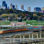 Kansas City MO skyline in evening and moving train in foreground.