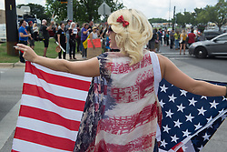 August 29, 2017 - A woman hold up an American flag during a protest welcoming president Donald Trump to Austin where he visited the emergency operations center assisting Hurricane Harvey. (Credit Image: © Sandy Carson via ZUMA Wire)