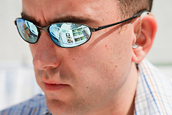 Man with hearing impairment studying book reflected in sunglasses.