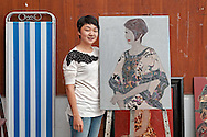 HCMC Fine Arts student poses with her lacquer painting, Ho Chi Minh City, Vietnam, Southeast Asia. Lacquer painting, son mai in Vietnamese, was developed as its own art form separate from wood finishing and is an important traditional technique taught in the Fine Arts University of Ho Chi Minh City.
