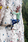 Young teen girl climbs up an artificial climbing wall