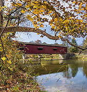 The 148-foot wooden Cataract Falls Covered Bridge was built in 1876 at the Upper Falls of Mill Creek (formerly known as Eel River) and was open to automobile traffic until 1988. The bridge now serves pedestrians and was extensively repaired starting in 2000. It is the only remaining covered bridge in Owen County. Cataract Falls State Recreation Area is an hour southwest of Indianapolis, near Cloverdale, Indiana, USA. The bridge was designed with a Smith's High Double Wood Truss (Smith Type 4), prefabricated in Toledo, Ohio and shipped disassembled for reassembly. Vibrant autumn foliage colors glowed for this panorama stitched from 5 overlapping photos captured October 21, 2015.