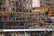 American builders work on a balance on scaffolding working on a building site in Chelsea, New York City; New York, United States of America.